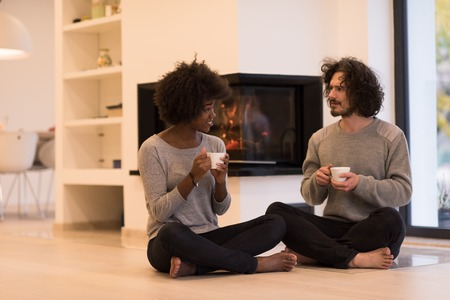 Young romantic multiethnic couple sitting on the floor in front of fireplace at home, looking at each other, talking and drinking coffee autumn day Stock Photo