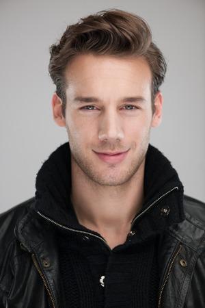 Mode man, Knap ernstige schoonheid mannelijk model portret dragen lederen jas, jonge kerel over grijze achtergrond