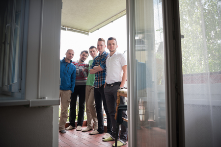 group of men: portrait of a group of men standing on the balcony