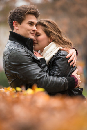 jovenes enamorados: love, relationship, family, season and people concept - smiling couple hugging over autumn natural background