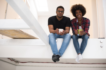 renovating: Happy young African American couple having break during moving to new house