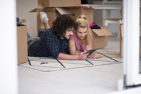 redecoration: Young couple in love moving in a new flat, lying on the floor and surfing the web on a tablet computer in search of new redecoration ideas Stock Photo