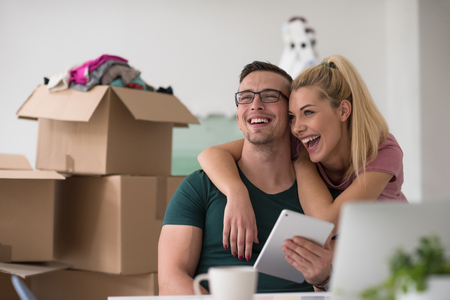 them: Young couple moving in a new home. Man and woman at the table using notebook laptop computer and plans with boxes around them