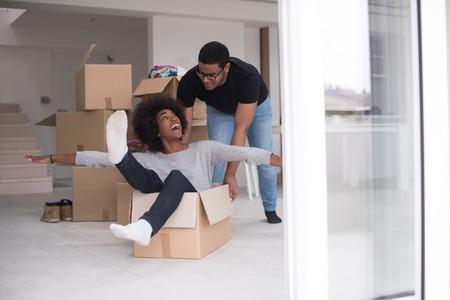 梱包材、新しい家に移動した後楽しんで遊んでボックスに座っているアフリカ系アメリカ人のカップル