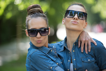 identical: Young beautiful twin sister with sunglasses in identical wardrobe posing in a park on a sunny summer day Stock Photo