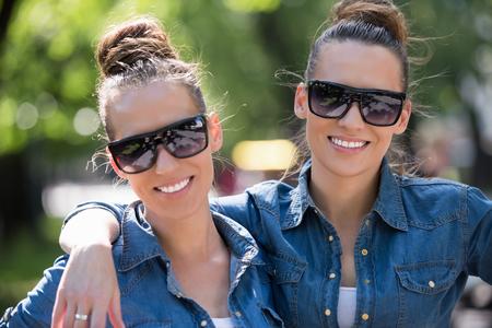 belle jeune s?ur jumelle avec des lunettes de soleil dans une armoire identiques posant dans un parc sur une journée d'été ensoleillée Banque d'images