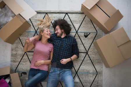 Top view of attractive young couple moving, holding hands, looking at camera and smiling while lying among cardboard boxes Stockfoto