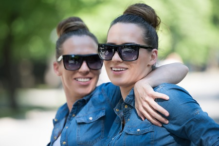 Young beautiful twin sister with sunglasses in identical wardrobe posing in a park on a sunny summer day Stock Photo