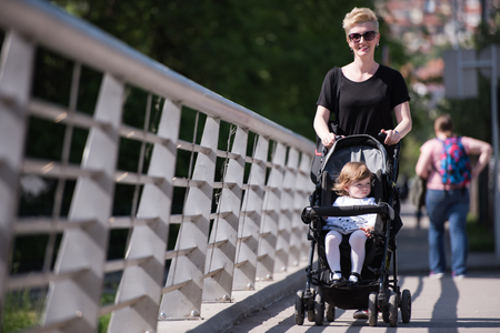 empujando: beautiful young mother with blond hair and sunglasses pushed her baby daughter in a stroller on a summer day Foto de archivo