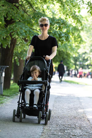 beautiful young mother with blond hair and sunglasses pushed her baby daughter in a stroller on a summer day Stock Photo