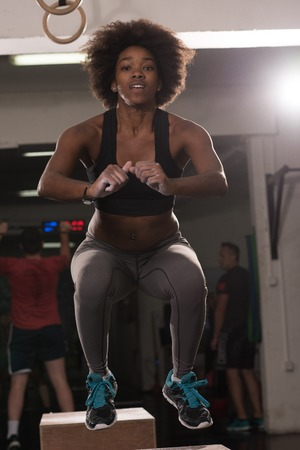 Fit young african american woman box jumping at a crossfit style gym. Female athlete is performing box jumps at gym. Foto de archivo