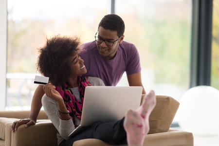 Gelukkig jong Afrikaans Amerikaans paar die online door laptop winkelen die creditcard thuis gebruiken