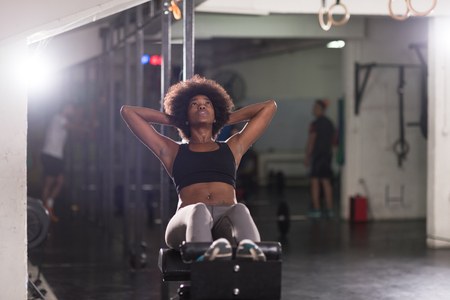 sit on studio: young fit african american woman doing sit ups in fitness studio at the gym.Abdominal exercises Sit up Stock Photo