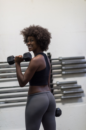 young beautiful African American woman doing bicep curls in a gym Stock Photo