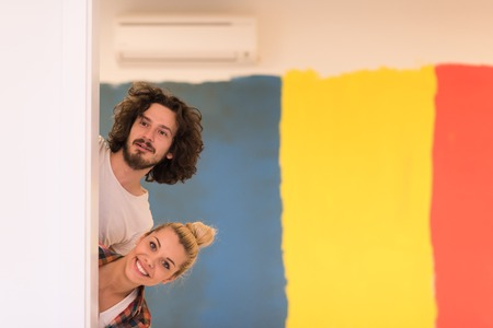 fun at work: portrait of happy smiling young couple painting interior wall of new house  peeking from behind the wall Stock Photo