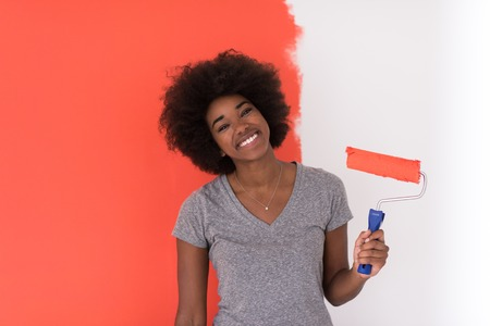 american house: portrait of a young beautiful African American woman painting wall in her new apartment