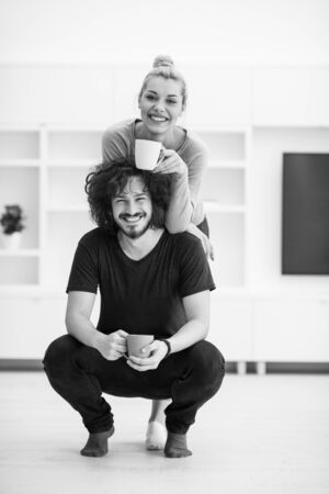 renovated: Portrait of a happy young beautiful couple hugging and drinking coffee in their new home