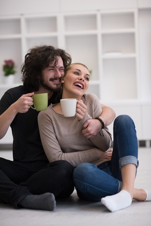 young happy couple: portrait of young happy beautiful couple sitting on the floor and drinking coffee in their new home
