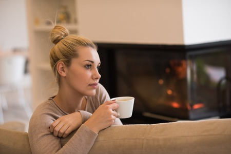 fireplace living room: Portrait of beautiful young woman with a mug near a fireplace