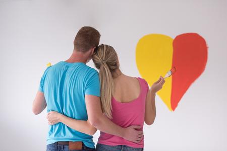 若い幸せなカップルは、自宅の修復をしながら壁にハートを描いています。