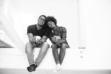 black couple: Happy young African American couple having break during moving to new house