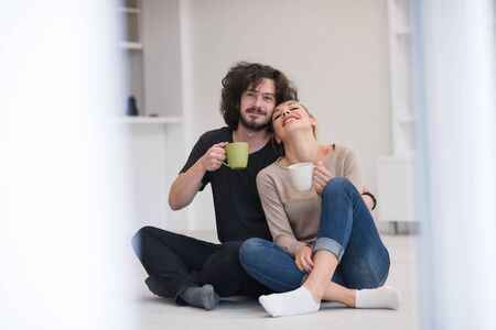 renovated: portrait of young happy beautiful couple sitting on the floor and drinking coffee in their new home