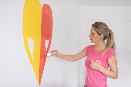 Young woman painting a heart on the wall while doing repair at home. Imagens
