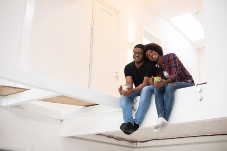 move in: Happy young African American couple having break during moving to new house