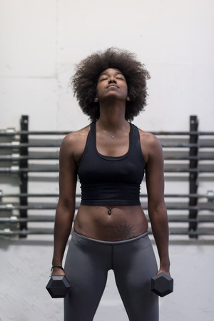 black grip: young beautiful African American woman doing bicep curls in a gym Stock Photo