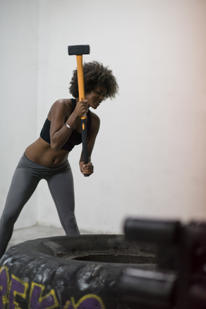 Sledgehammer Tire Hits african american woman workout at gym with hammer and tractor tire Stock Photo