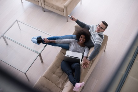 Young multiethnic couple relaxing on the sofa in the luxury living room, using a laptop and remote control