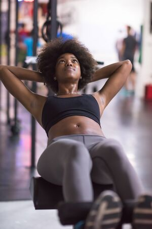 situp: young fit african american woman doing sit ups in fitness studio at the gym.Abdominal exercises Sit up Stock Photo