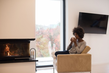 fireplace living room: Happy joyful african american woman drinking cup of coffee relaxing at fireplace. Young black girl with hot beverage heating warming up. autumn at home. Stock Photo