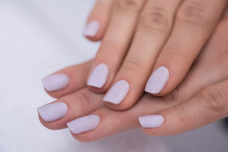 nailcare: Beautiful fingers with french manicure on the towel. Manicure in a beauty salon.