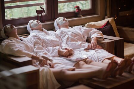 face mask: beautiful young women  getting facial clay mask at spa, lying with cucumbers on eyes