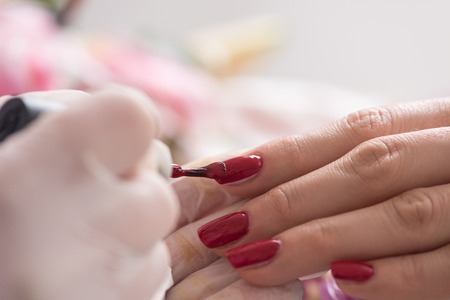 nailcare: Woman hands receiving a manicure in beauty salon. Nail filing. Close up, selective focus.