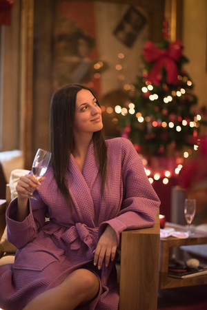spa woman: people, and relaxation concept   beautiful young woman in bath robe drinking champagne at spa over holidays lights background