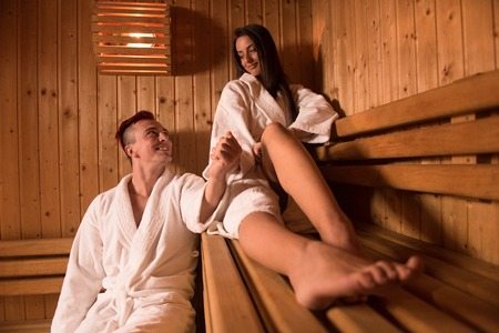 Portrait of a young happy beautiful couple enjoys relaxing in the sauna