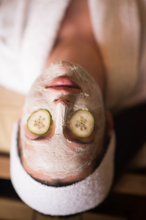 Beautiful young woman is getting facial clay mask at spa, lying with cucumbers on eyes Stock Photo