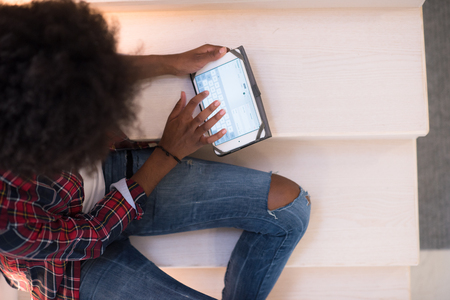 electronic tablet: Attractive young black woman using her electronic tablet while sitting on a staircase