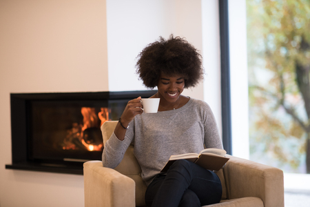 アフリカ系アメリカ人女性は、暖炉のそばで読書コーヒーのカップを飲みます。若い黒女の子ホット飲料を暖める暖房をリラックスします。秋の自
