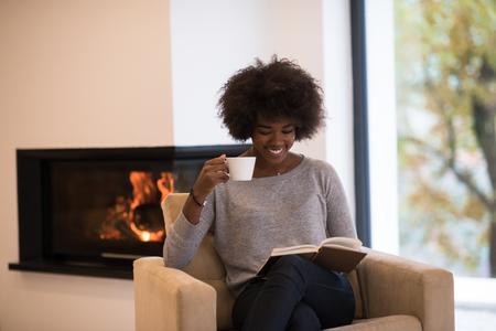African American Frau trinken Kaffee Lesebuch am Kamin. Junge schwarze Mädchen mit heißem Getränk Heizung Erwärmung entspannen. Herbst zu Hause.