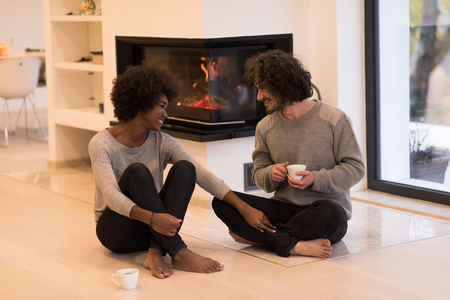 black couple: Young romantic multiethnic couple sitting on the floor in front of fireplace at home, looking at each other, talking and drinking coffee at autumn day
