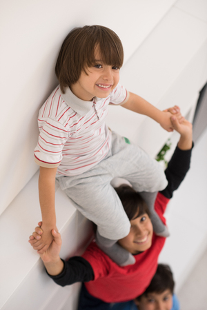 young boys: happy young boys having fun and posing line up piggyback in new modern home top view Stock Photo