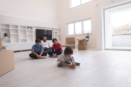 portrait of happy young boys with their dad sitting on the floor in a new modern home Stock Photo