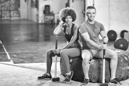 portrait of a young multiethnic couple after training with a sledgehammer and tractor tire