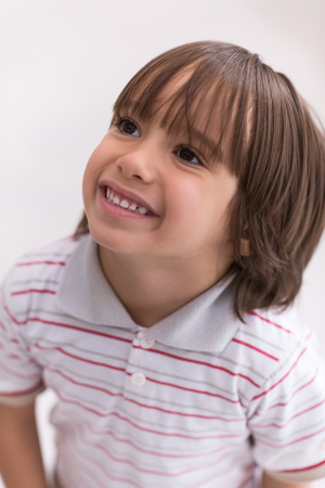 Portrait of happy joyful beautiful little boy who looking up isolated on white background