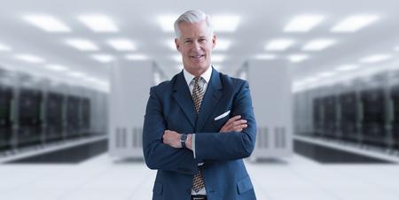 isp: Portrait of senior businessman in big rack server room Stock Photo