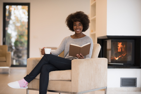woman in black: african american woman drinking cup of coffee reading book at fireplace. Young black girl with hot beverage relaxing heating warming up. autumn at home.