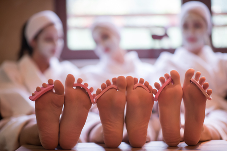 famale: group of famale friends in spa have fun, celebrate bachelorette party with face mask